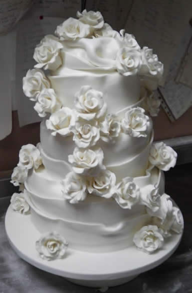 Beautiful white icing roses cascading down a stunningly iced wedding cake made by a Wedding Cake Professional in Kent